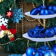 Christmas decorations on dessert stand, on  color wooden background — Foto de Stock