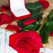 Beautiful red rose with ring on wooden table close-up — Stock Photo
