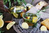Chaleira e xícara de chá com gengibre na bandeja tecida de saco na mesa de madeira — Fotografia Stock