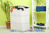 Full laundry basket on wooden floor on home interior background — Foto Stock