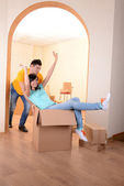 Young couple fooling around in new house on room background — Foto Stock
