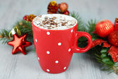 Hot chocolate with cream in color mug, on table, on Christmas decorations background — Foto Stock