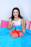 Beautiful woman with gift in bed on Valentine Day — Stock Photo