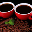 Red cups of strong coffee with coffee beans and chocolate bars close up — Stock Photo