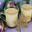 Cups of eggnog with fir branches and Christmas decorations on wooden background — Stock Photo