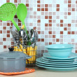 Dishes and cutlery in kitchen on table on mosaic tiles background — Stock Photo