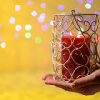 Candle in hand on blur lights background — Foto Stock