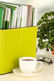 Magazines and folders in green box,on office interior background — Stock Photo