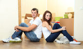 Young couple with boxes in new home on room background — Stok fotoğraf