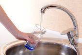 Hand holding glass of water poured from kitchen faucet — Foto Stock