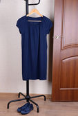 Dress hanging on hanger near door — Stock Photo