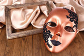 Mask on golden fabric on wooden background — Stok fotoğraf