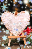 Decorative heart on easel, on wooden table, on shiny background — Stock Photo