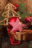 Weihnachtsschmuck in korb und fichte filialen auf tisch mit braunen hintergrund — Stockfoto
