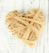 Decorative heart of straw, on wooden background — Stock Photo