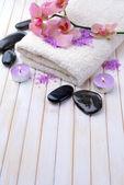 Bodegón con hermosa floración orquídea flor, toalla y tazón de fuente con sal marina, sobre fondo de madera color — Foto de Stock