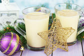 Cups of eggnog with fir branches and Christmas decorations on table close up — Stock Photo