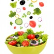 Fresh mixed vegetables falling into bowl of salad isolated on white — Stock Photo