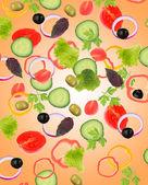 Falling fresh vegetables on orange background — Stockfoto