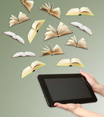 Tablet and opened books on grey background — 图库照片
