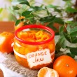 Stock Photo: Orange jam with zest and tangerines, on brown wooden table