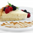 Slice of cheesecake with berries and sauce on plate, isolated on white — Stock Photo