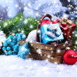 Composition with Christmas decorations in basket, fir tree on light background — Stock Photo