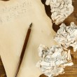 Stock Photo: Crumpled paper balls with ink pen and music sheet on wooden background