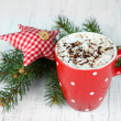 Hot chocolate with cream in color mug, on table, on Christmas decorations background — Stock Photo #36575771