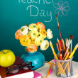 School supplies and flowers on blackboard background with inscription Teacher Day — Stock Photo #36575853