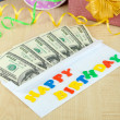 Dollar bills in envelope as gift at birthday on wooden table close-up — Stock Photo #36575969
