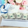 Dollar bills in envelope as gift at wedding on wooden table close-up — Stock Photo #36575989