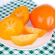 Stock Photo: Ripe persimmons on plate close-up