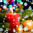 Composition with Burning candle, fir tree and Christmas decorations on multicolor lights background — Stock Photo #36577259