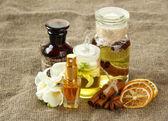 Garrafas com ingredientes para o perfume sobre fundo de serapilheira — Foto Stock