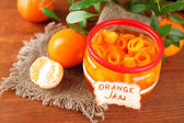 Orange jam with zest and tangerines, on brown wooden table — Stock Photo