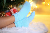 Legs in socks near Christmas tree on carped — Stock Photo