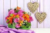 Composition de fleurs dans la caisse avec des coeurs décoratifs sur table sur fond en bois — Photo