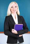 School teacher near blackboard with exercise book in classroom — Stock Photo