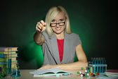Wicked chemistry teacher sitting at table on dark colorful background — Stockfoto