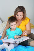 Little boy with mom read book in bed — Stock Photo