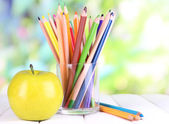 Colorful pencils in glass on wooden table on natural background — Foto Stock
