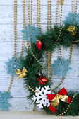Christmas wreath with decorations, on color wooden background — Stock Photo