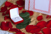 Ring surrounded by roses and petals on wooden table close-up — Stock Photo