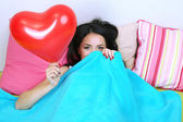 Beautiful woman with balloon in bed on Valentine Day — Stock Photo