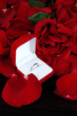 Ring surrounded by rose petals on wooden table close-up — Stock Photo