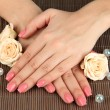 Woman hands with pink manicure and flowers, on bamboo mat background — Stock Photo