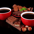 Red cups of strong coffee and chocolate bars isolated on black — Stock Photo