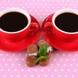 Stock Photo: Red cups of strong coffee and chocolate bars on polka dot background