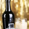 Baileys liqueur in bottle and glass on golden background — Stock Photo